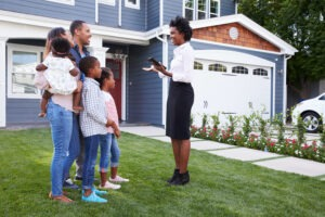 First Home Purchase - Female real estate agent speaking with a young family of 5 on a lawn in front of a beautiful home