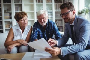 Older couple with lawyer looking at a document. Estate Planning, Wills, Power of Attorney