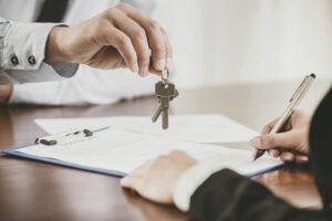 First Home: Agent handing keys to first time home buyer, while signing the mortgage