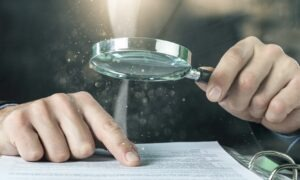 Home Ownership - Man with magnifying glass scrutinizing a contract with his index finger