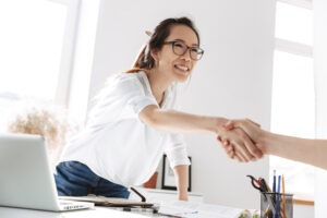 Home Ownership - Female asian mortgage specialist shaking hands with future first time home buyer