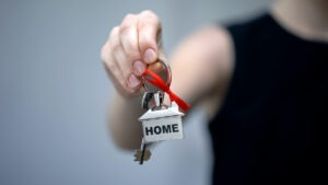 Home Ownership - The outreached had of a female real estate agent handing over a house key with a fob with 'home' written on it along with a red ribbon.