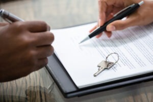 Renting vs. Buying - Close up image of two hands. A man's hand with a pen about to sign a contract and a woman's hand pointing where to sign, next to house keys on the contract.