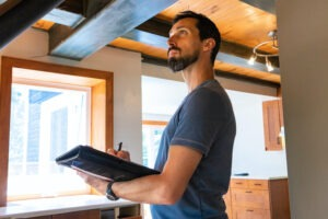 Renting vs. Buying - Male home inspector looking up towards ceiling with a clipboard writing inspection notes and observations.