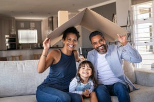 First Time Home Buyer - Young family of three. Mom and Dad with daughter holding a bent and peaked piece of cardboard like a roof over all of their heads.