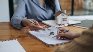 Home Ownership - Real estate lawyer discussing final house closing details and presenting keys to a first time home buyer.
