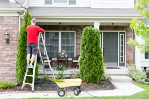 First Home: Homeowner on ladder making repairs to front of a house