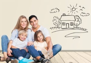 Renting vs. Buying - Young family of four sitting on a floor together next to a caricature drawing ion the wall of a house with a yard and trees and the sun shining on the house.